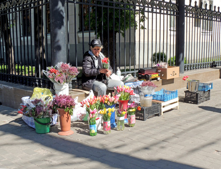 tradeswoman: Mid adult women selling flowers near railing at the street corner at a sunny day