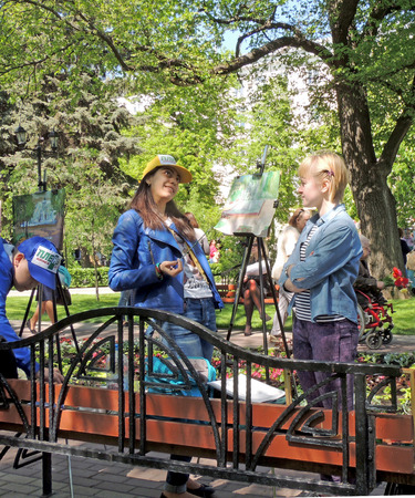 late teens: Friendly chat of drawing late teens students with brush in the hand near easel on the open outdoors lesson of art school on the city public garden during the Victory Day celebration