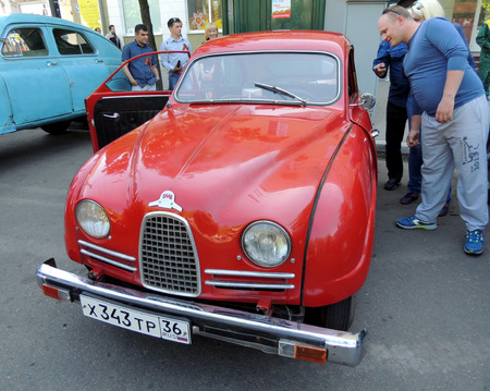 ve: City dwellers look round sweden retro car of 1950s frontwheel drive coupe Saab 93 on the street near city central square during the celebration of the Victory VE Day