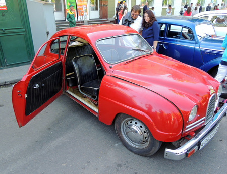 ve: City dwellers look round sweden retro car of 1950s frontwheel drive coupe Saab 93 with open door on the street near city central square during the celebration of the Victory VE Day
