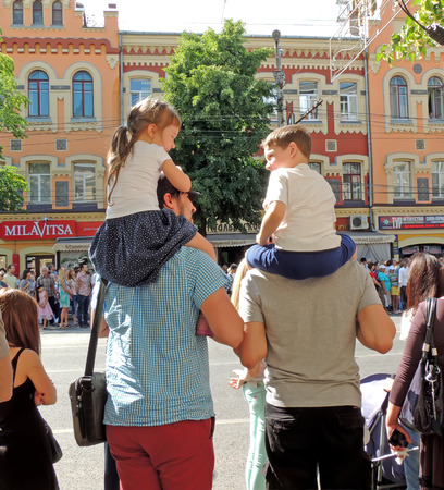 elementary age girl: Communication of elementary age girl and boy sitting on fathers shoulders. City dwellers on the parade of Street Theatres on the Platonov Arts Festival Editorial