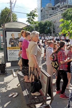shoeless: Mature women standing shoeless on the street bench with handbag. City dwellers look the street parade of Street Theatres on the Platonov Arts Festival