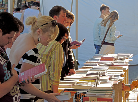 acquaint: Customers take a good look at a new books on the Book Fair on city square Editorial