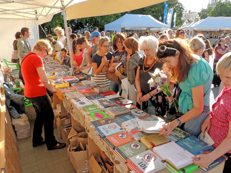 acquaint: Customers look through a new books on the Book Fair in city square Editorial