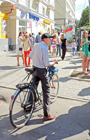 mature men: Mature men standing with bicycle on a sidewalk watches street parade of Street Theatres on the Platonov Arts Festival