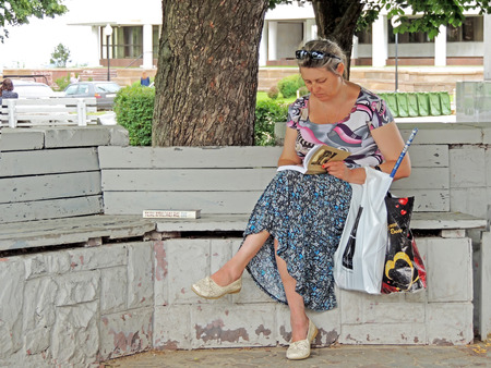 purchased: Mature adult women with glasses on the top of head and plastic bags on the arm reading a purchased book under a tree on a park bench during the Book Fair on city public garden