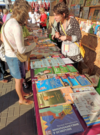 acquaint: Woman customer with the purchased book talk with saleswoman of marquee with Books for children on the Book Fair on city square Editorial