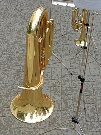aerophone: Tuba and music stand with musical notation on the pavement in the rain