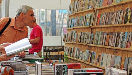 acquaint: Senior men choose a book in a stall on the Book Fair Editorial