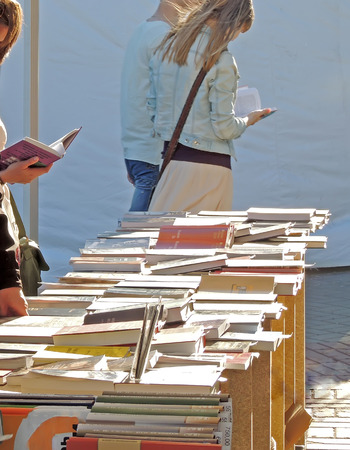 acquaint: Customers take a good look at a new books on the Book Fair on city square Stock Photo