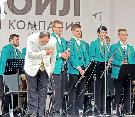 an obeisance: Conductor and his musicians on the performance on the Music Festival of Childrens Brass Bands in the city square Editorial