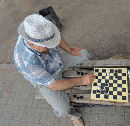 mature men: Mature men with hat playing chess on the bench Stock Photo