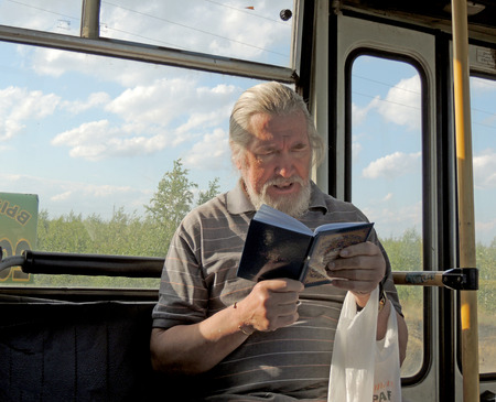 mature men: Grey-haired  bearded mature men reading a book in the bus in the suburb of Voronezh Editorial