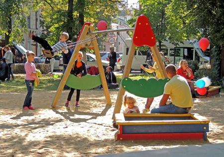children at play: Elementary age and pre-adolescent children have fun on the playground with their parents in a city park Editorial