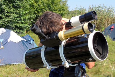 grassy plot: The man watching the sky through a telescope at the campsite