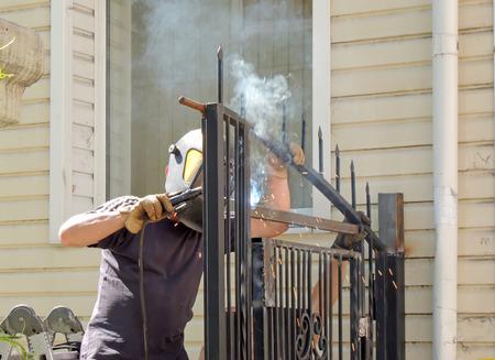 herramientas de trabajo: Trabajador que suelda puerta de metal de un edificio de apartamentos en la calle Foto de archivo