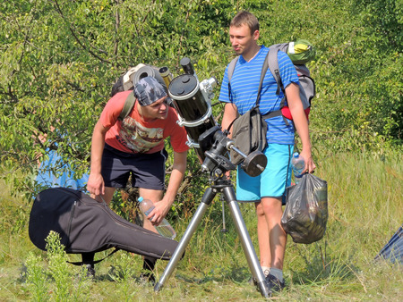 grassy plot: Young men interested in astronomy at the campground Editorial