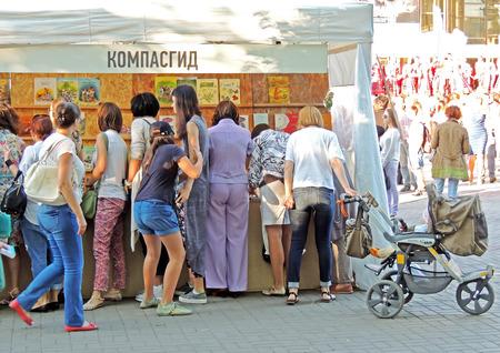 Femmes examiner attentivement chapiteau avec la littérature infantile sur la Foire du livre sur la place de la ville