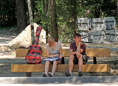 music book: Girl and guy with guitar and music book sitting on the park bench during its reconstruction