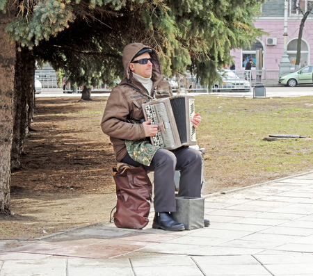 mature men: Mature men sitting on the camp stool in the street and playing the accordion