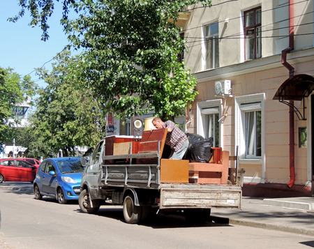 sack truck: Mature men on the body of utility truck with open tailgate engaged in loading outmoded furniture in the city street
