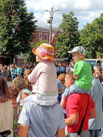 elementary age girl: Elementary age girl and boy sitting on the their fathers shoulders and looking parade of Street Theatres on the Platonov Arts Festival on the city street
