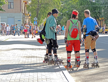 kneepad: A group of mature men rollerblading on the city street on a holiday Editorial