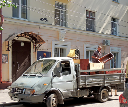 outmoded: Mature men with shelf on the body of utility truck on the city street engaged in loading outmoded furniture