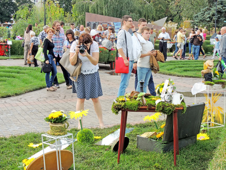 garden city: Woman photographs the exposure on the city square during the international exhibition-fair Voronezh - Garden City Editorial