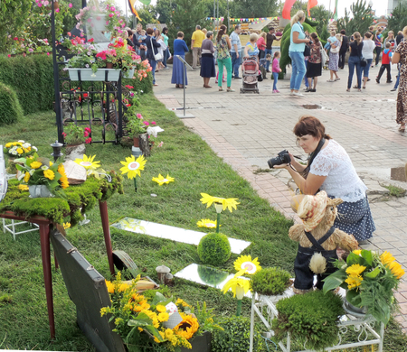 grass plot: Mid adult woman photographing exposition on the city square during the international exhibition-fair Voronezh - Garden City