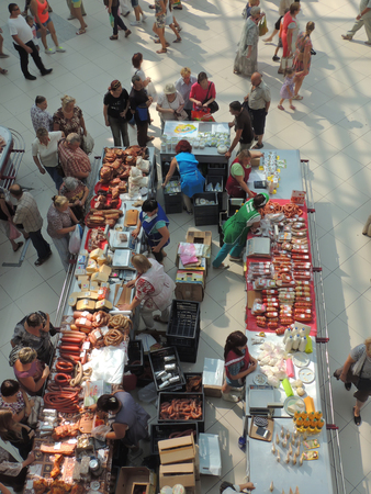 salespeople: Buyers are shopping sausages and dairy products in the city food market