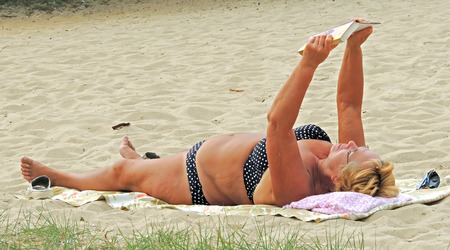 Mature woman in a swimsuit reading a book in the lying position on the beach Editorial