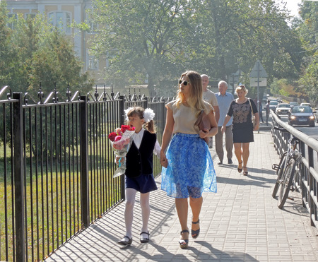 girl tied: A young adult woman with sunglasses and handbag under arm and a yawning pre-adolescent girl tied in a bows with a bouquet of flowers walk down the sidewalk holding hands Editorial