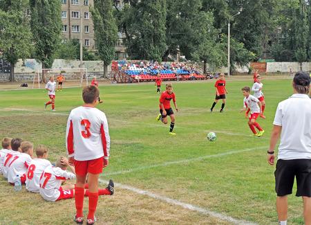 futbol infantil: adolescentes que se sientan en la hierba. benchwarmers ver un partido de fútbol en la competición de clubes de fútbol de los niños Editorial