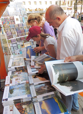 acquaint: Customers take a good look at a books of paintings by artists on the street stand in the city park