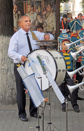 bass drum: Mature man playing the bass drum in the brass band composition on the city street during the celebration of the City Day