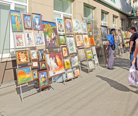 sidewalk talk: Two men conversing at the exhibition and sale of paintings on the sidewalk of the street