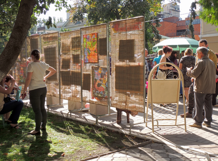 sidewalk talk: On the underside of the stand with exhibition and sale of paintings on the city street during the celebration of the City Day