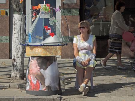 beine spreizen: Verkäuferin der Zuckerwatte auf einem Stuhl sitzen verteilt während der Feier der Tag der Stadt ihre Beine auf dem Gehweg der Stadt Straße