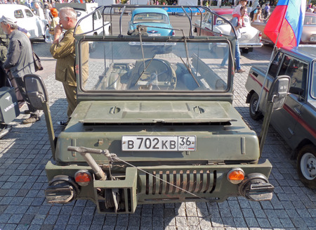 armaments: Forebody of the retro car of 1970-80s soviet military 4x4 amphibious cargo of Airborne Troops LuAZ-967 without top up on the stone paving city central square during the celebration of the City Day