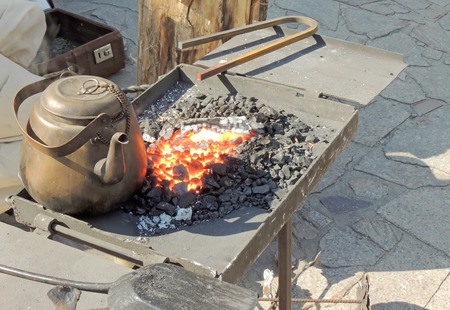 forge: Age-old copper kettle on the blacksmith forge fire