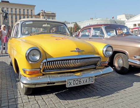 sidelight: Urban community around soviet executive car of 1960s sedan GAZ M21 Volga Third Series at the vintage car parade on the city central square Editorial