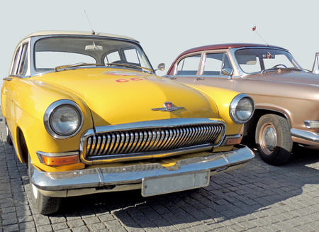sidelight: Retrocars of 1960s sedan on the cobbled pavement of the city central square at the parade of the vintage cars