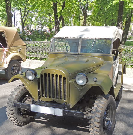 sidelight: Retrocar of World War II soviet military all-wheel-drive vehicle light truck F4 layout GAZ-67 with top up on the city core during the celebration of the Victory VE Day Editorial