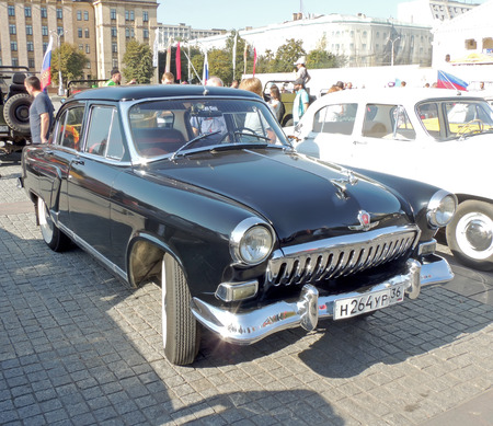 sidelight: Urban community around soviet executive car of 1960s sedan GAZ M21 Volga the Second Series Shark at the vintage car parade on the city central square