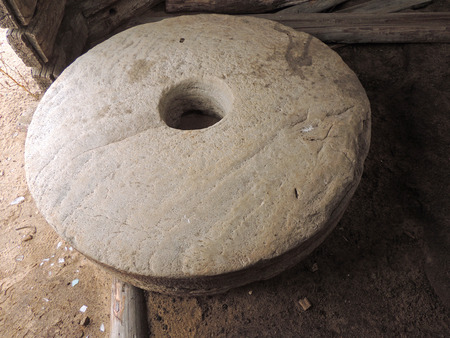 orifice: Millstone on the ground inside an old dilapidated old log mill Stock Photo