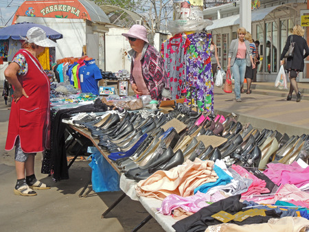 sidewalk talk: Street sale of clothing and ladies shoes. Street retail saleswoman talk on the city sidewalk Editorial