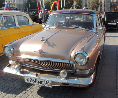 sidelight: Soviet executive car of 1960s sedan GAZ M21 Volga the Third Series Baleen brown color with leaping deer hood ornament. Vintage car parade on the city central square Editorial