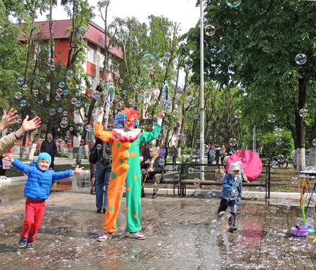 literary: Children trying to catch bubbles created by the clown in the town square during the literary festival