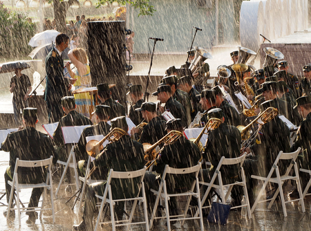 aerophone: Military brass band perform during a rainstorm. Central Avenue in the Park of VDNH, Moscow. International Military Music Festival Spasskaya Tower.